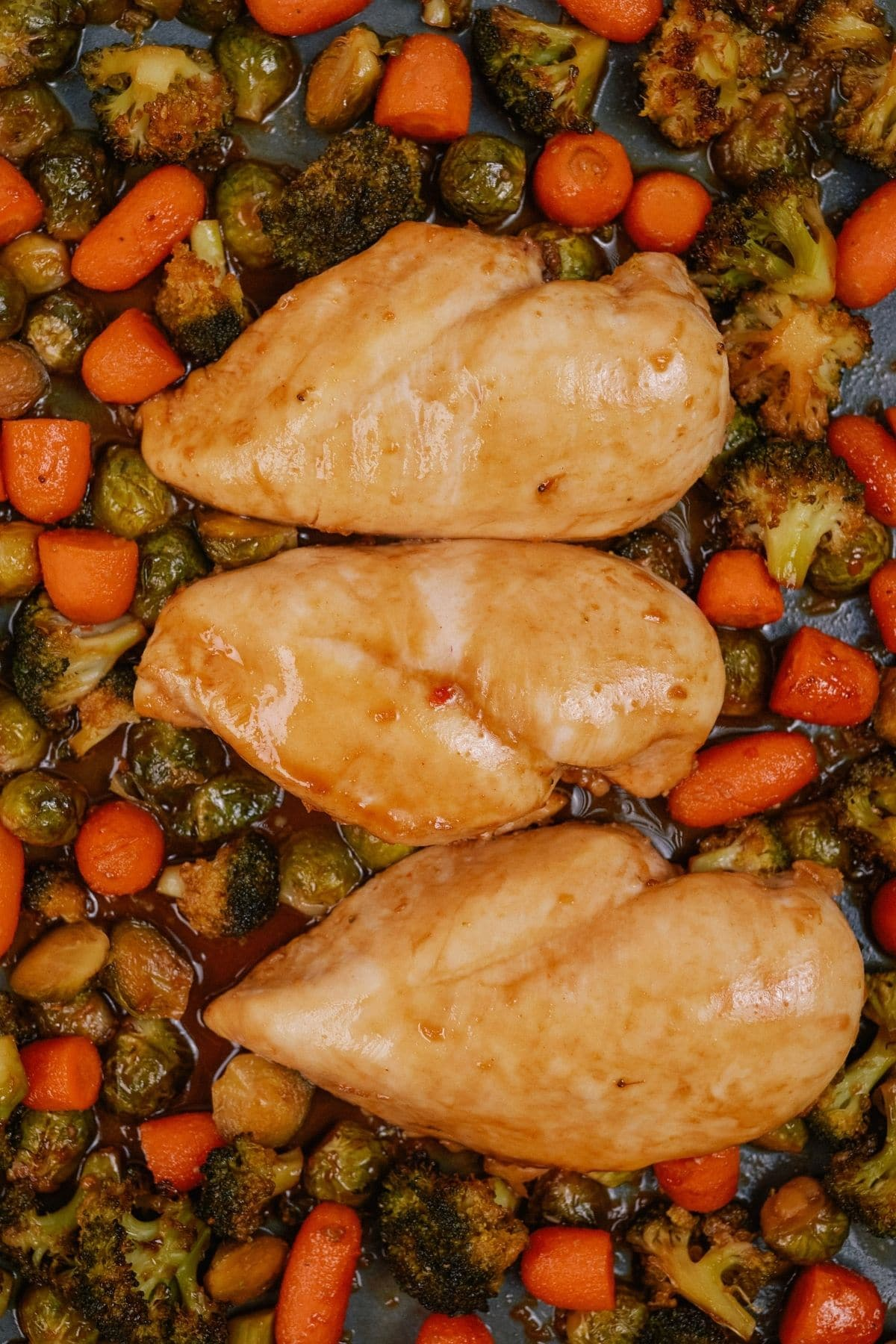 Image looking down at platter of chicken and carrots with broccoli