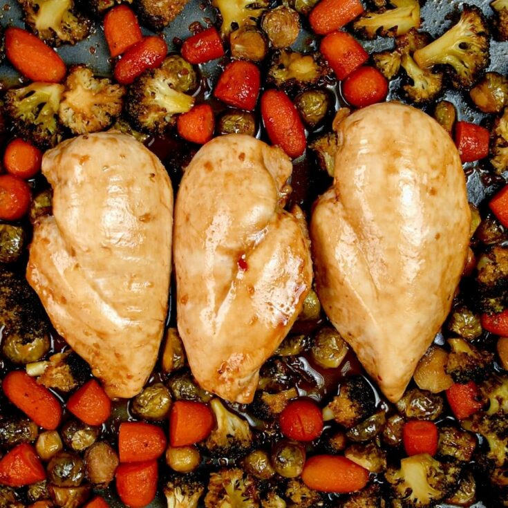 Three baked chicken breasts on baking sheet with brussels sprouts and carrots