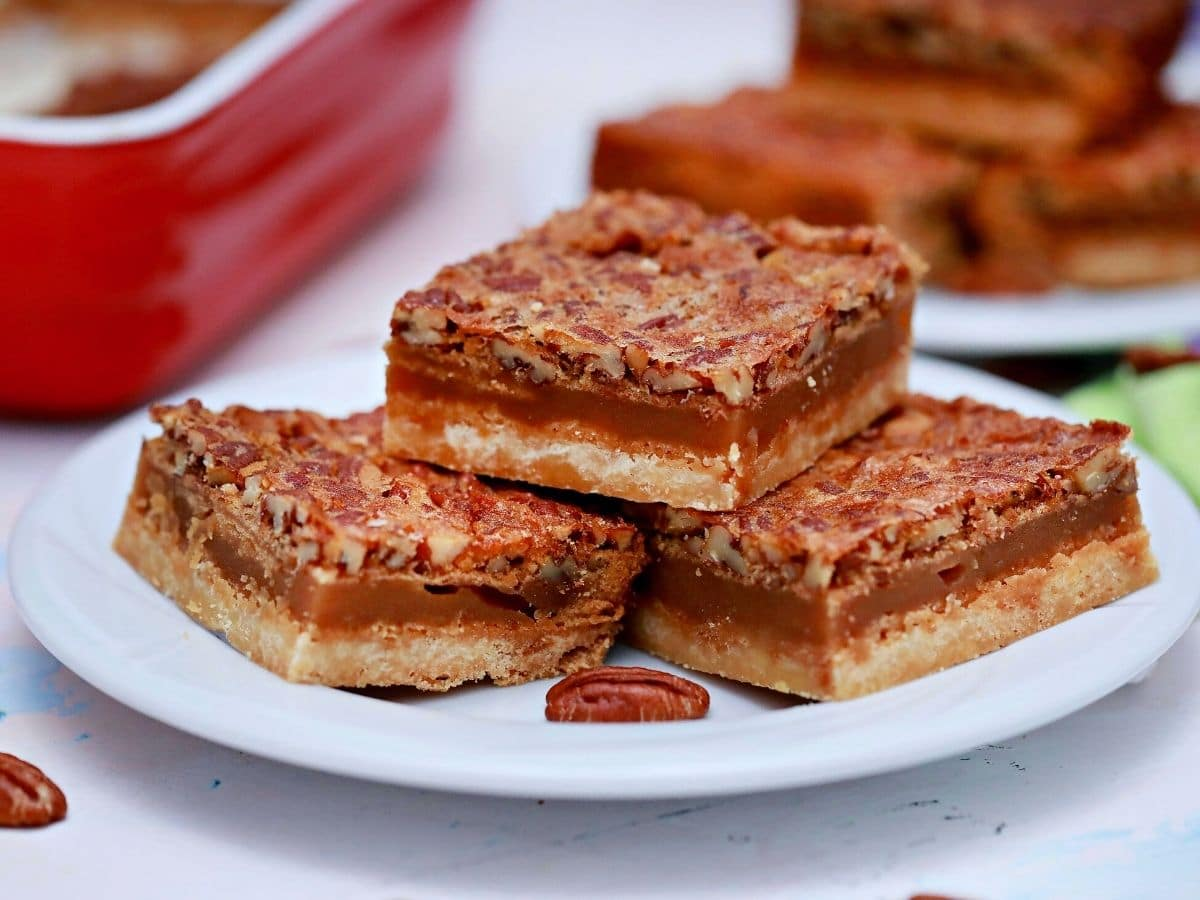Three pecan pie bars on white saucer by red baking dish