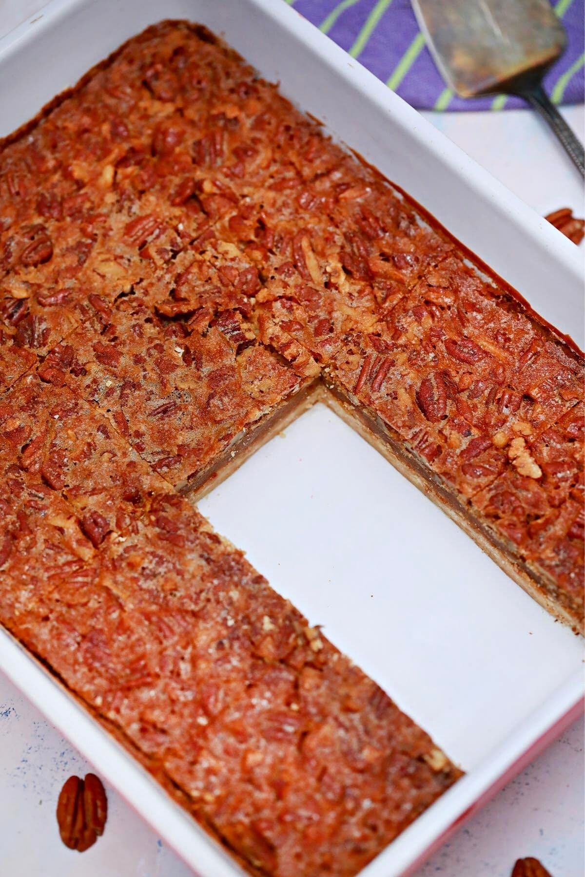 White baking dish of pecan pie bars with empty space where bars have been removed