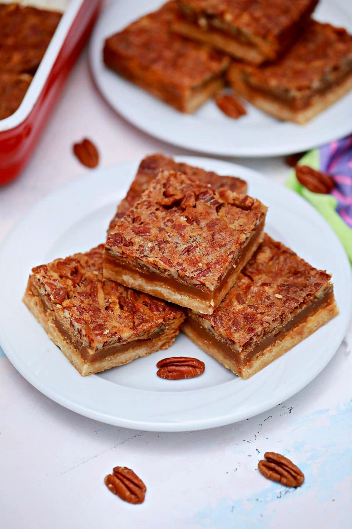 Two white saucers of pecan pie bars on table by red baking dish