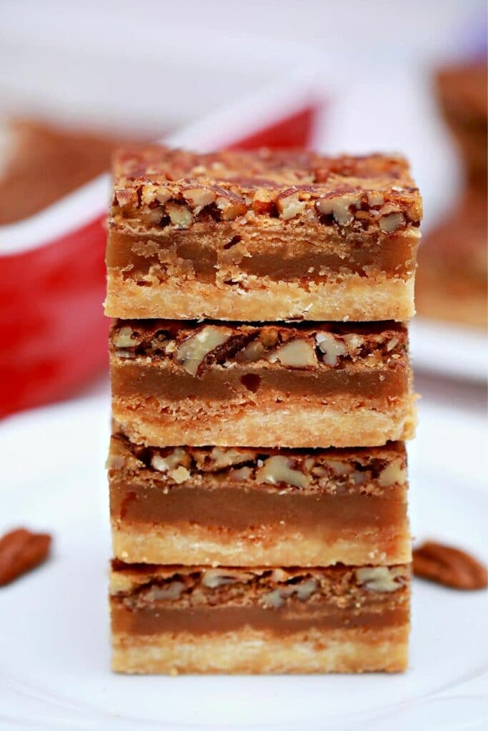 Square pecan pie bars stacked on white table by red baking dish
