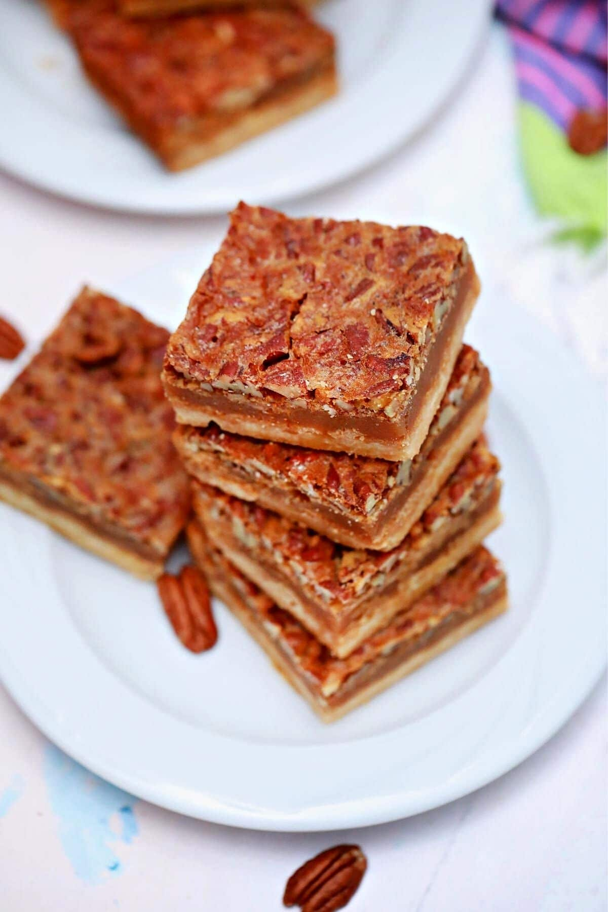 Two white plates holding sliced pecan pie bars