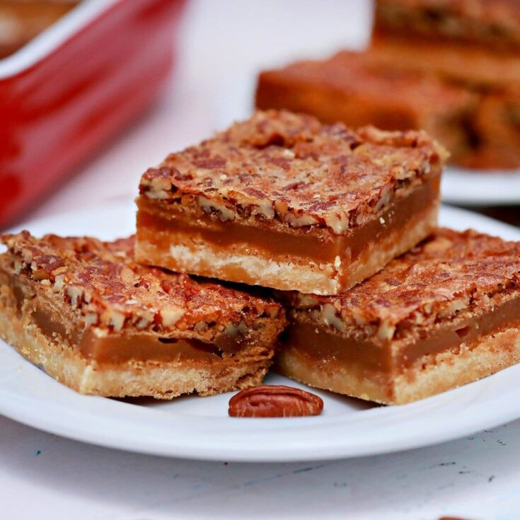 Three pecan pie bars on white plate by red baking dish