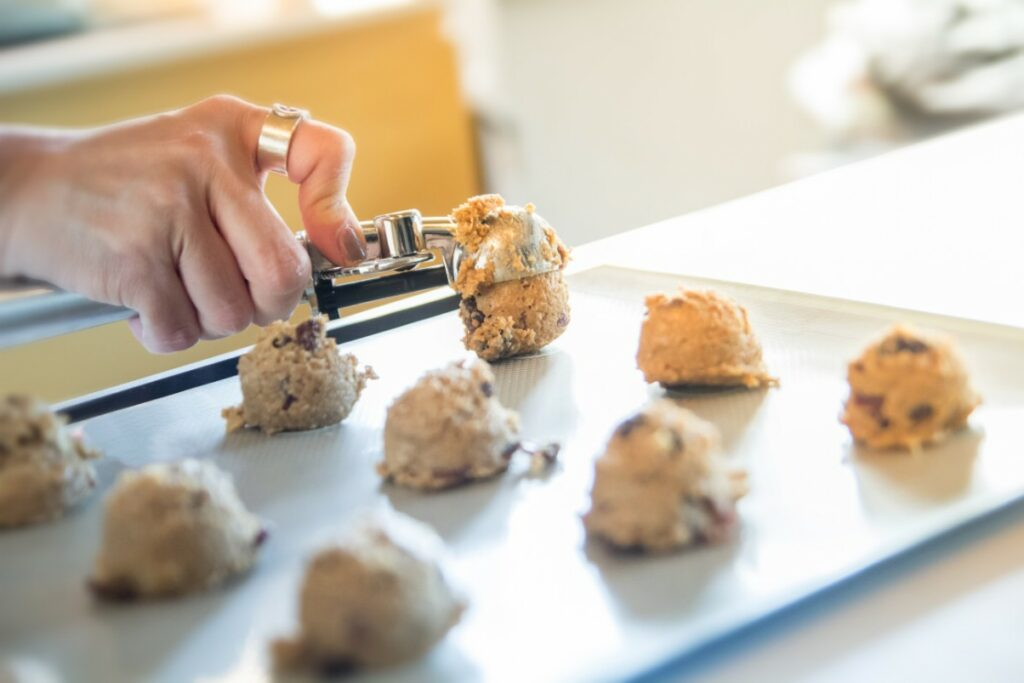 Portioning cookies using a cookie scoop in a baking tray.