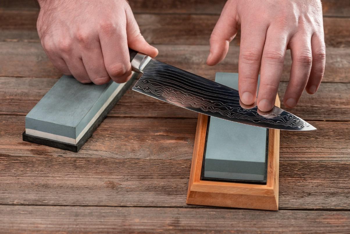 Chef sharpening damascus knife using professional sharpening tool.
