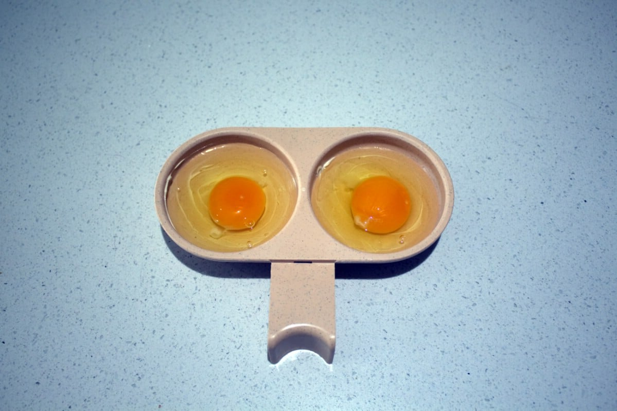 Silicone egg poacher with two eggs.