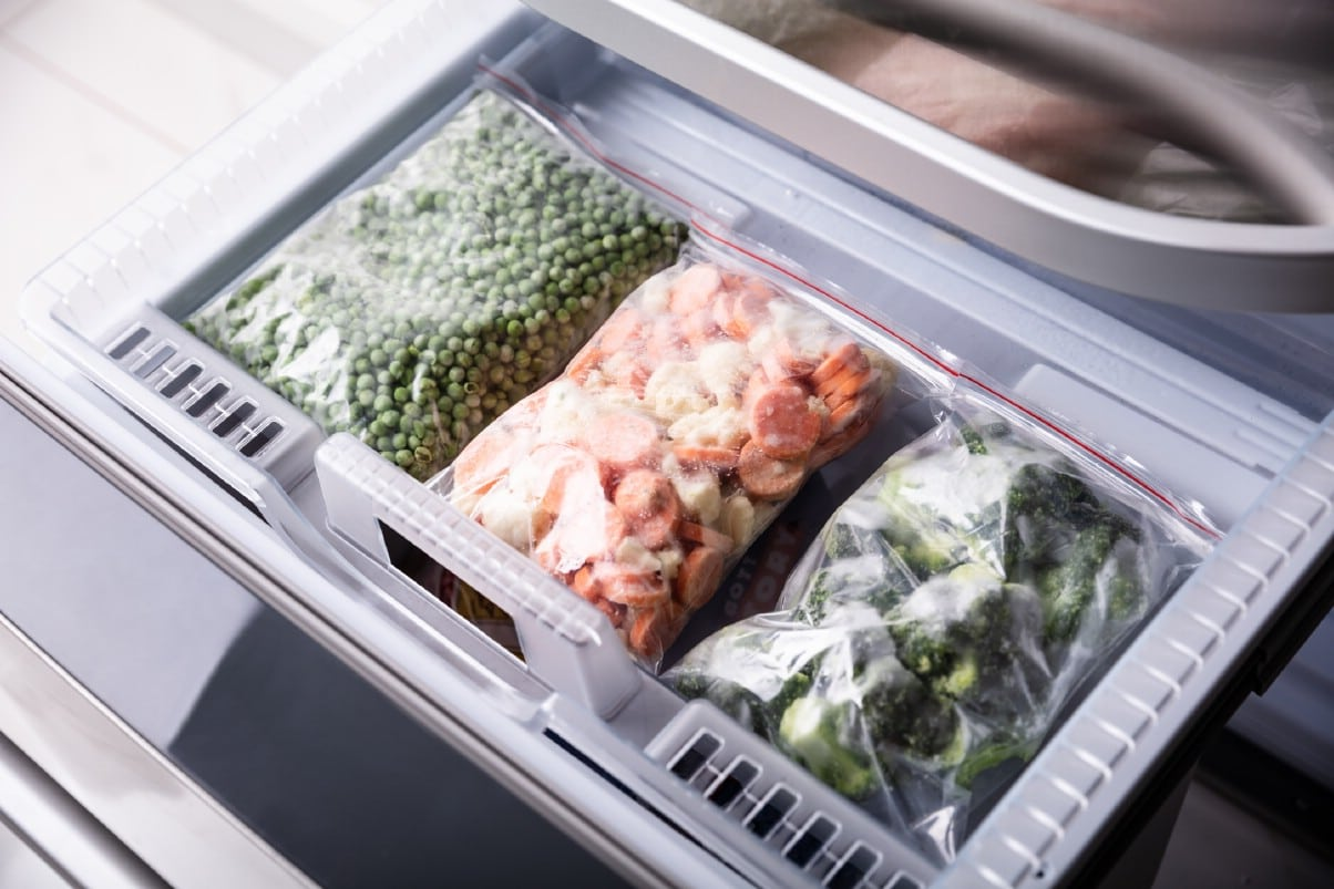 Frozen peas, carrots, and broccoli in refrigerator.