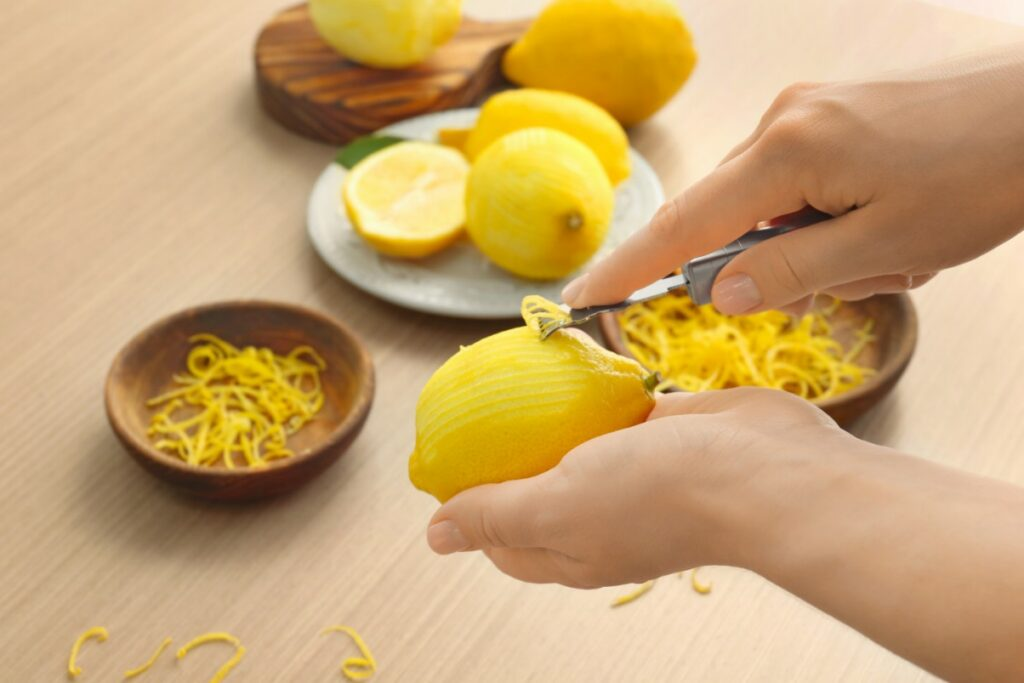 Using a zester to get lemon zest.
