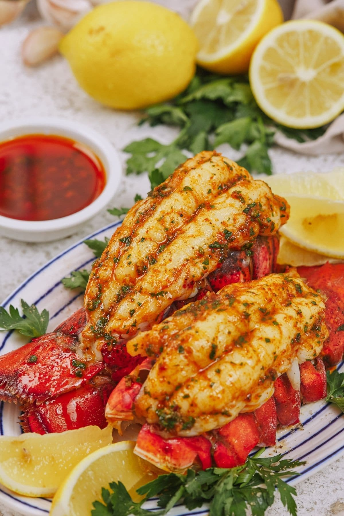 Lobster tails on plate net to bowl of butter sauce and sliced lemons