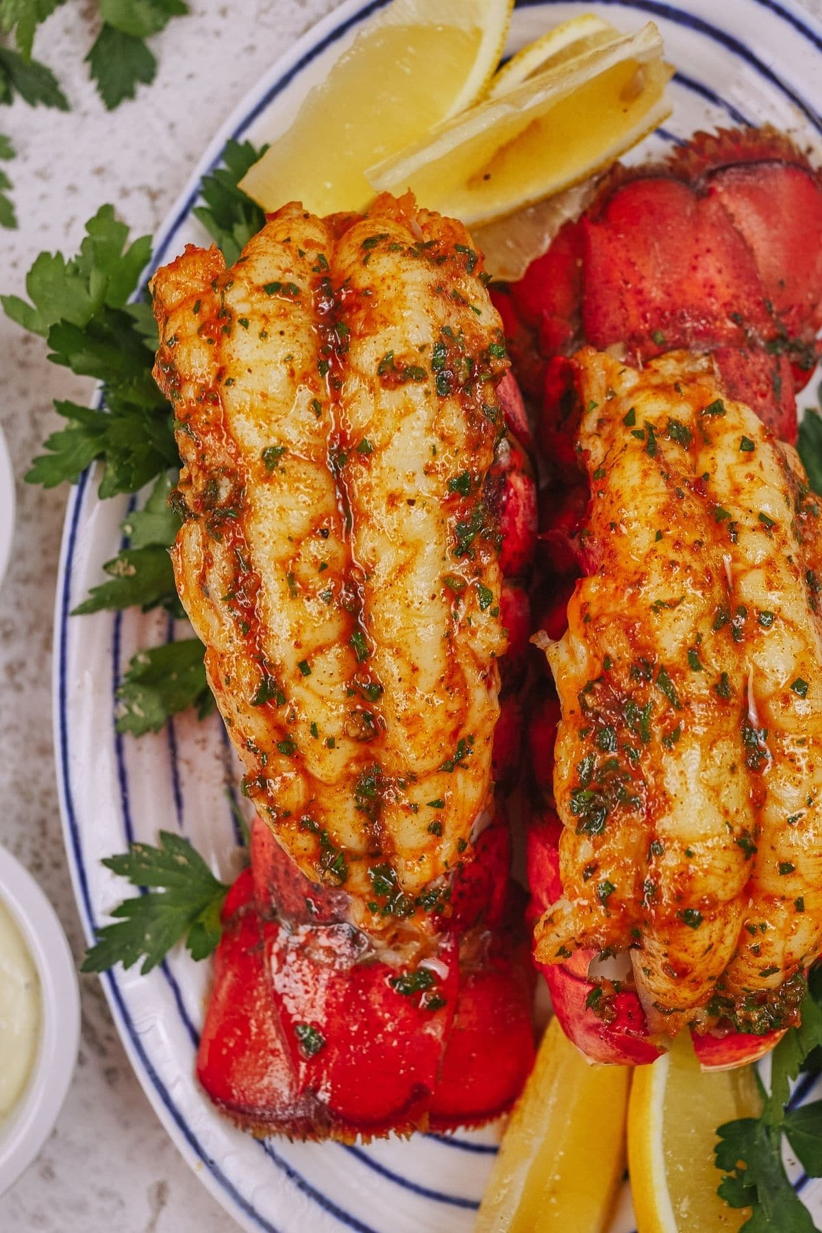 Lobster tails with lemon wedges and parsley on white and blue plate