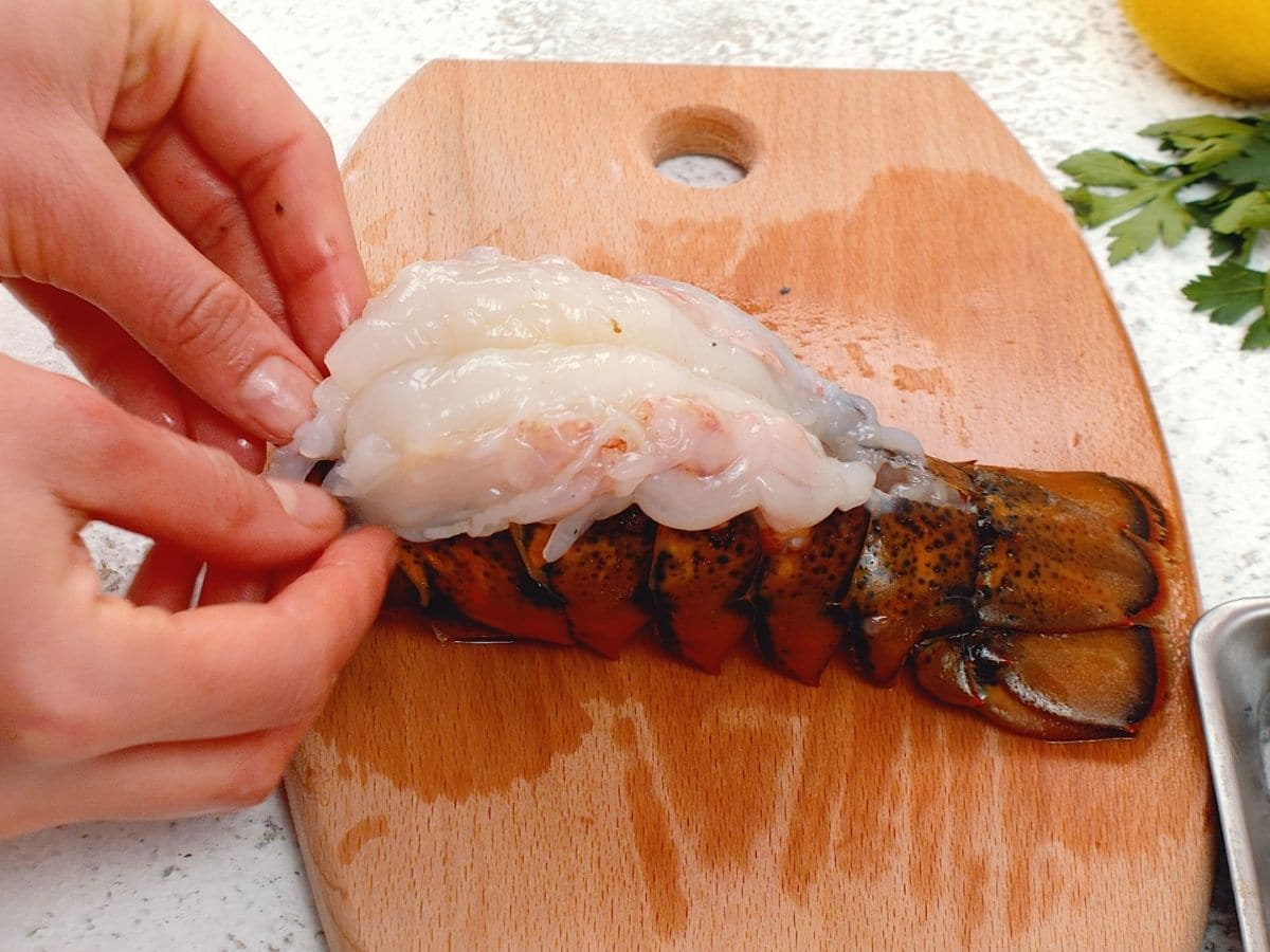 Hand putting lobster tail meat on top of lobster shell