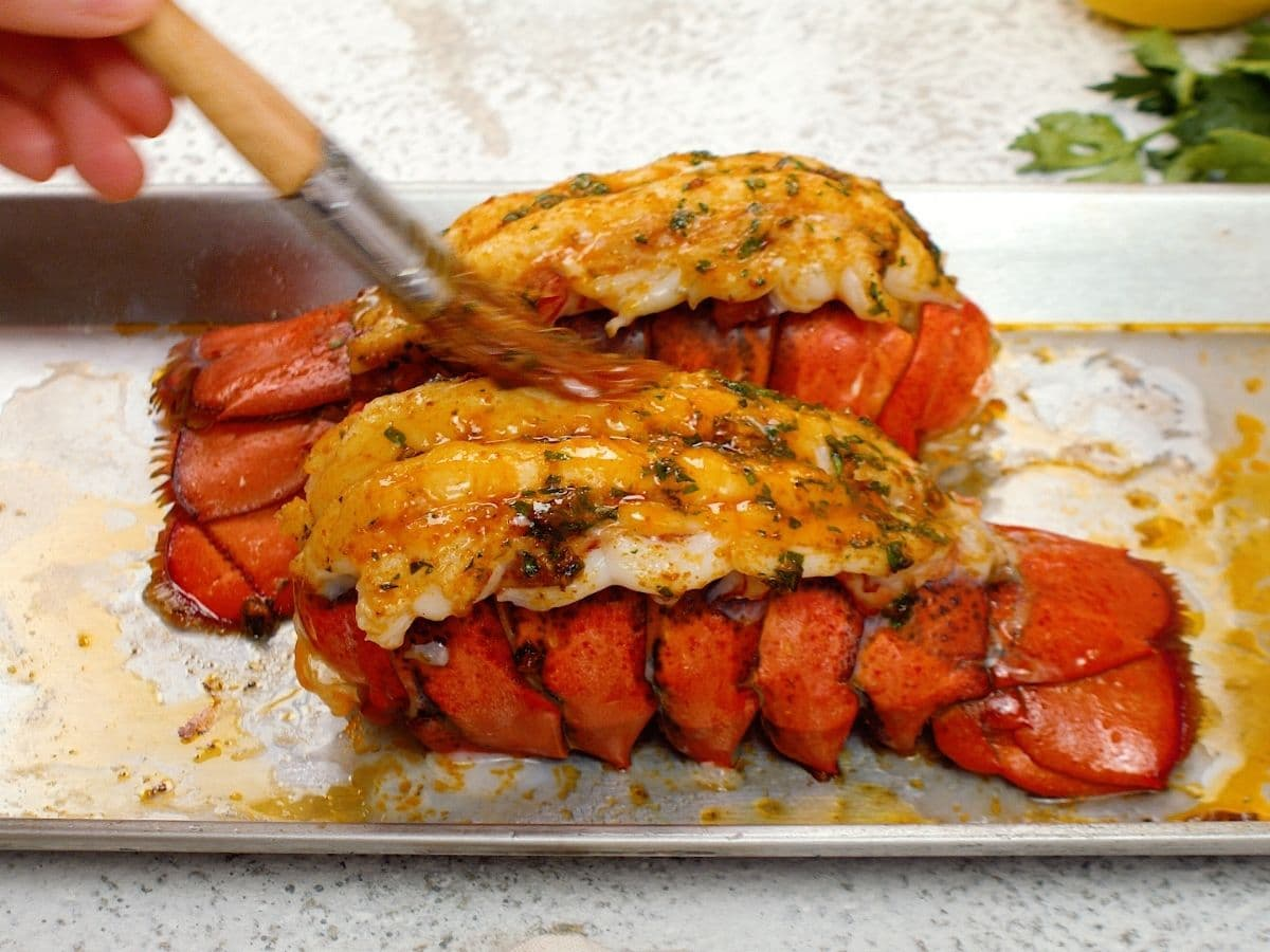 Hand brushing butter onto cooked lobster tails