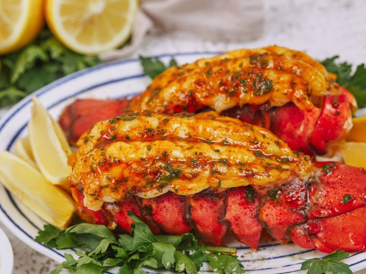 Lobster tails with herbed butter on white platter with lemon wedges
