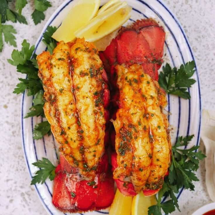 Two lobster tails on white and blue plate