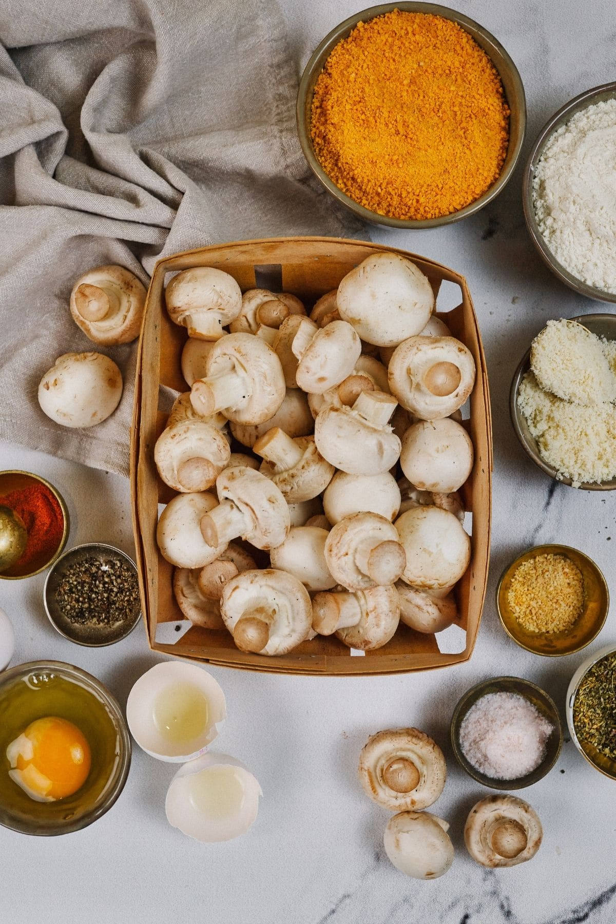 Mushrooms in basket in center of table surrounded by ingredients