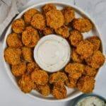 White plate of mushrooms around small bowl of white sauce