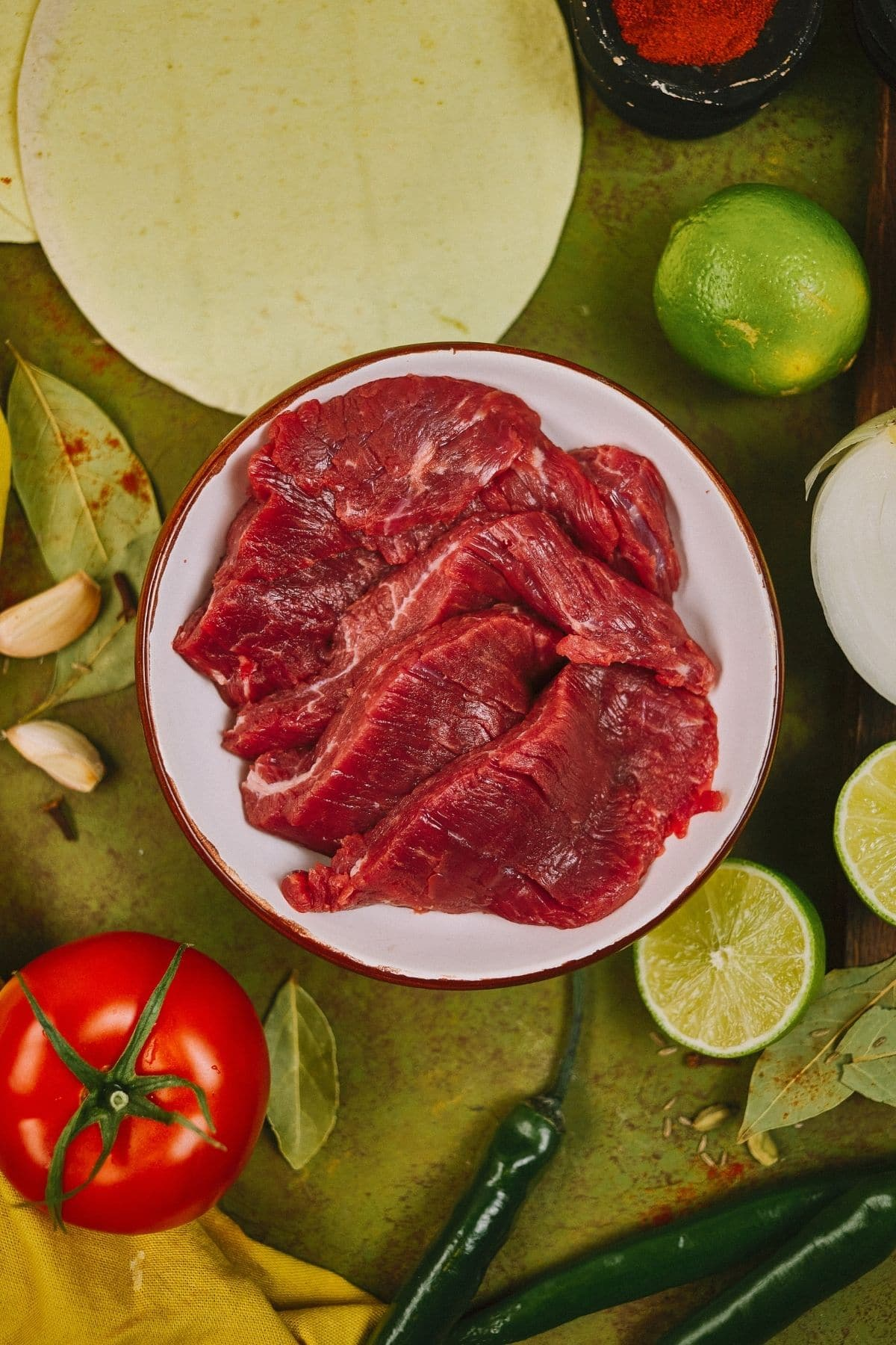 raw steak in white bowl on green table with tomato lime and tortillas