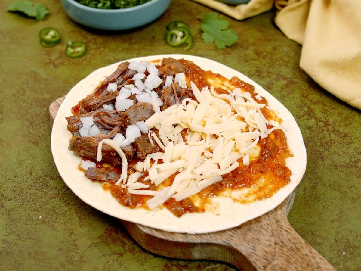 Onion and cheese on top of beef on tortilla