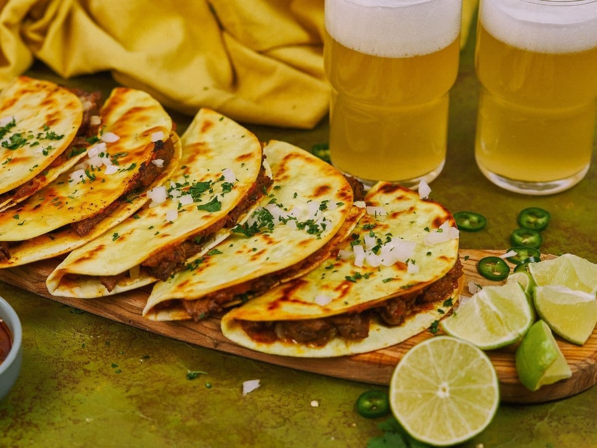 Tacos on board on green table next to mugs of beer