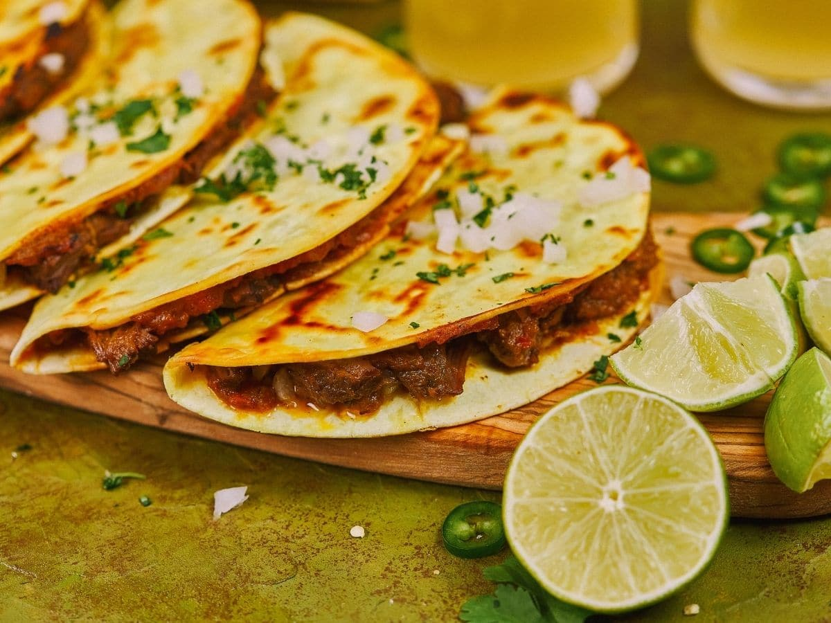 Birria beef tacos on wooden platter on green table by limes