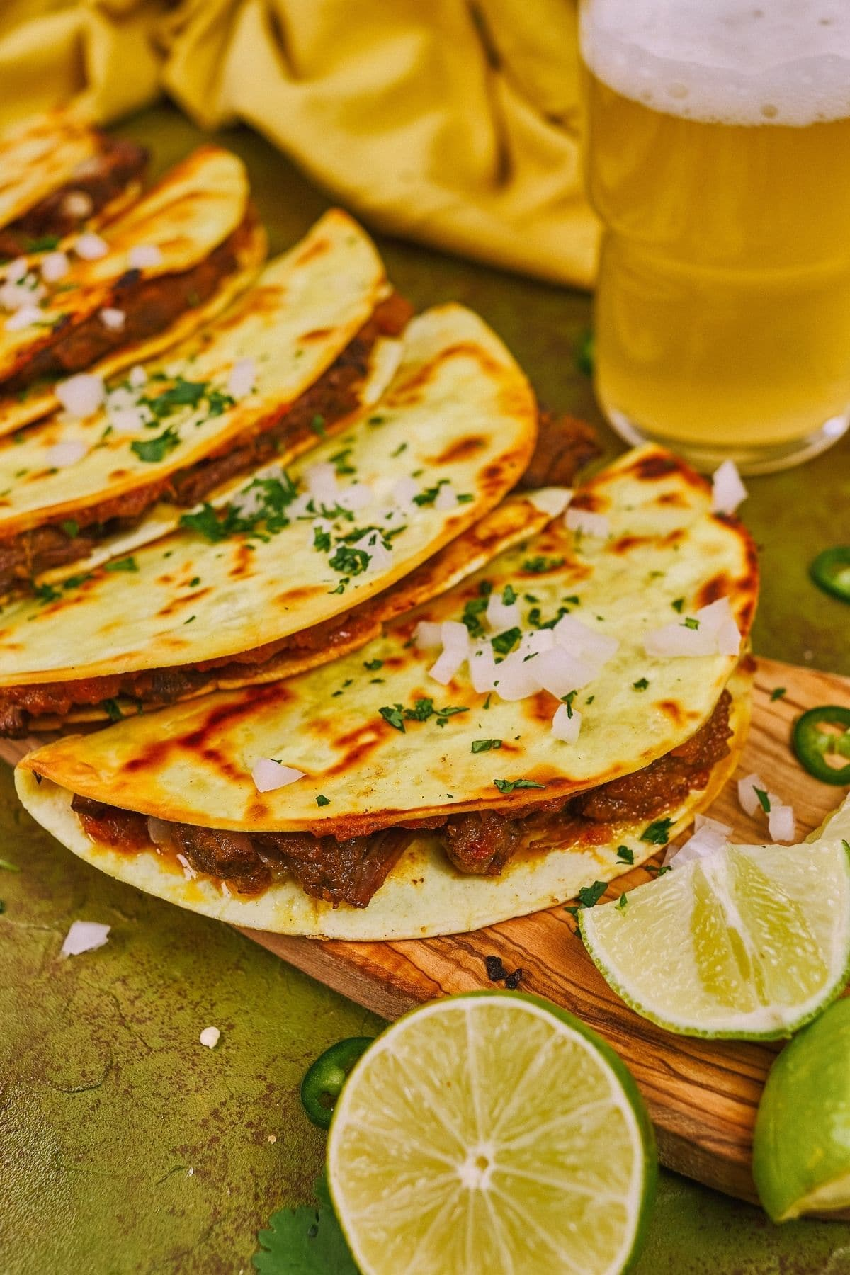 Tacos lined up on wooden board next to mug of beer