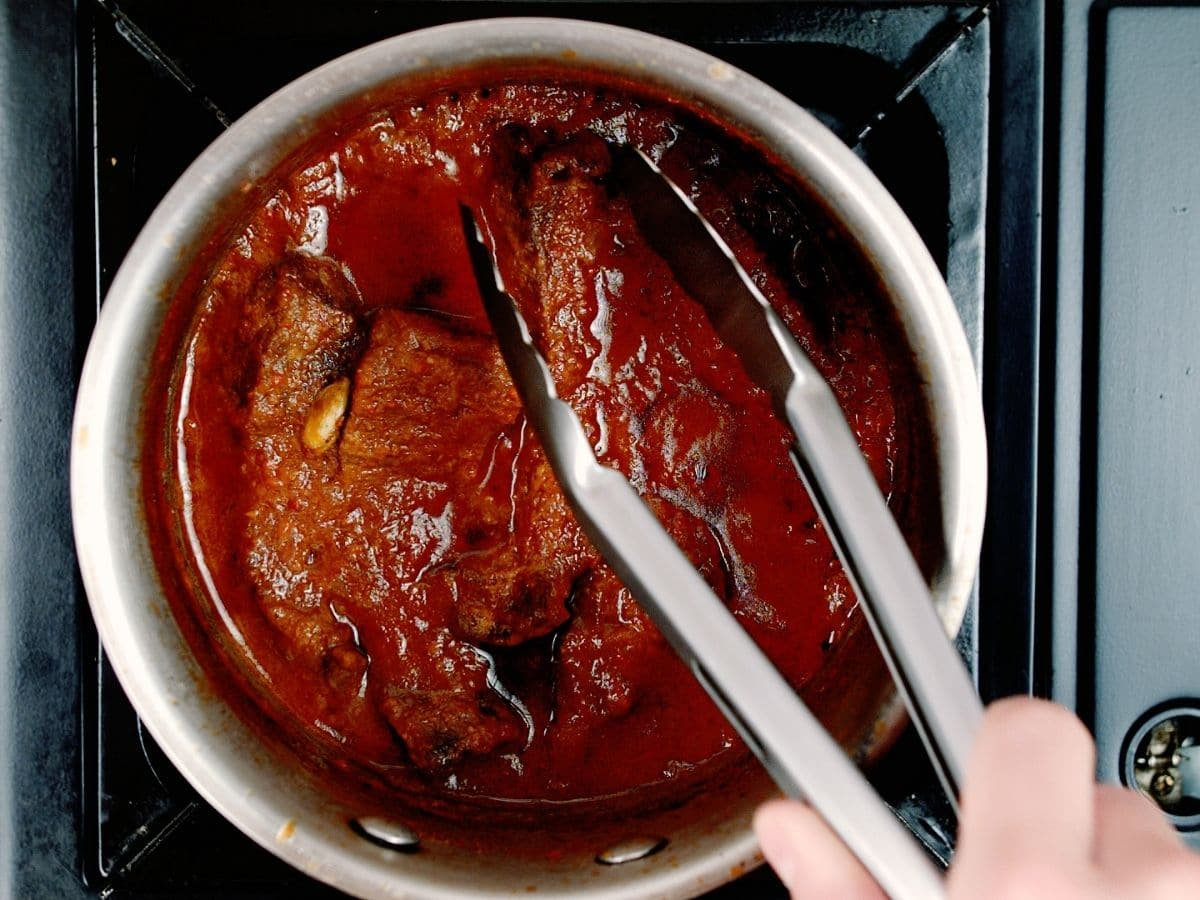 Tongs pulling beef out of dark red sauce in saucepan