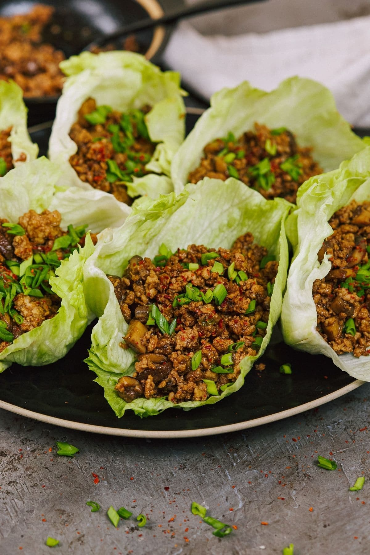 Lettuce filled with ground chicken sitting on black plate on brown counter