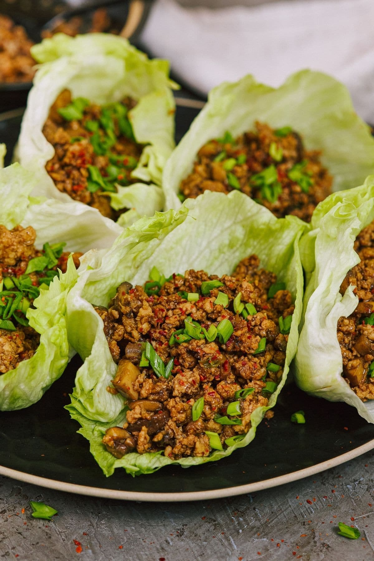 Black plate of lettuce wraps sitting on brown counter