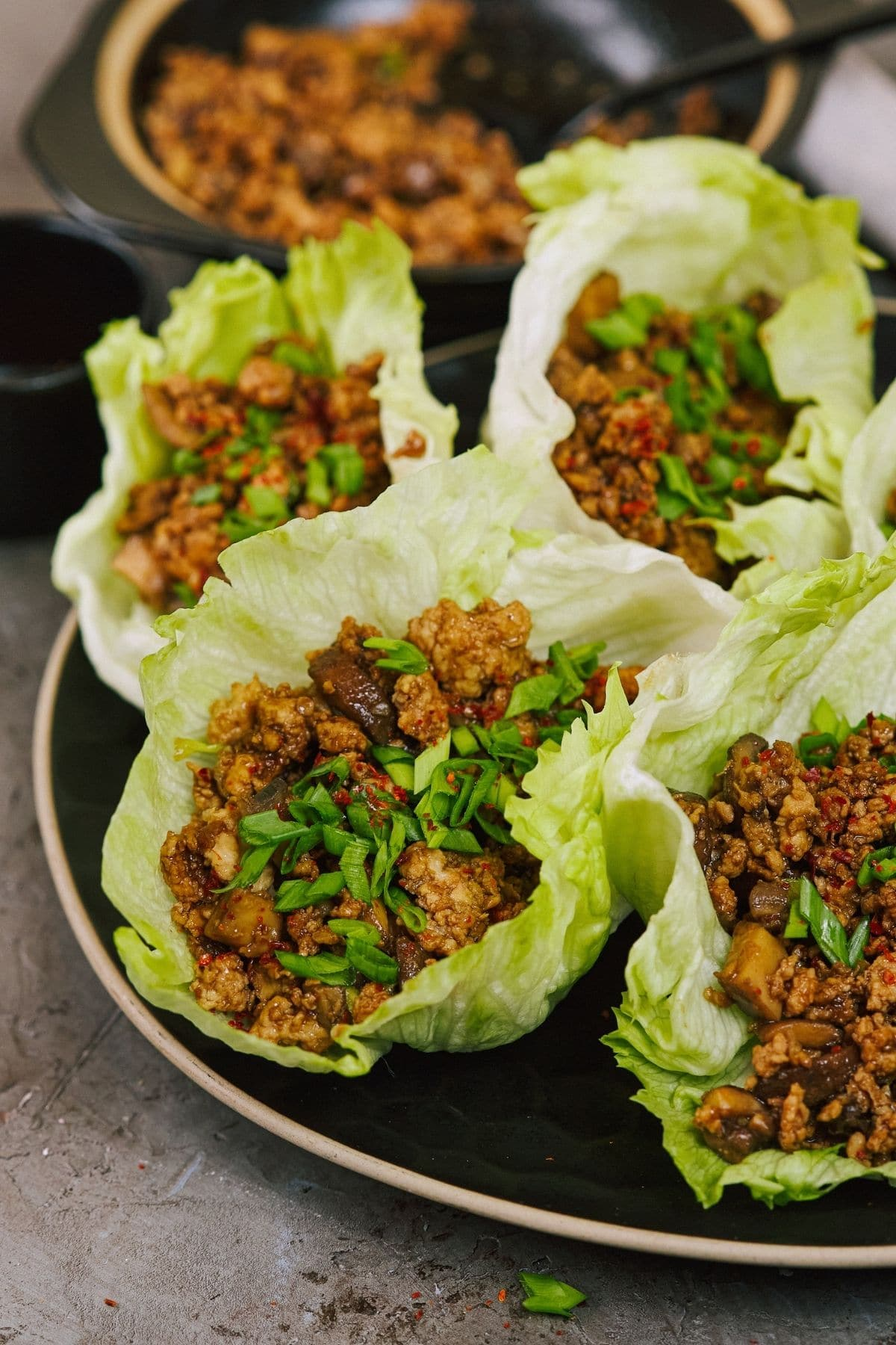 Multiple lettuce leaves filled with chicken mixture on plate