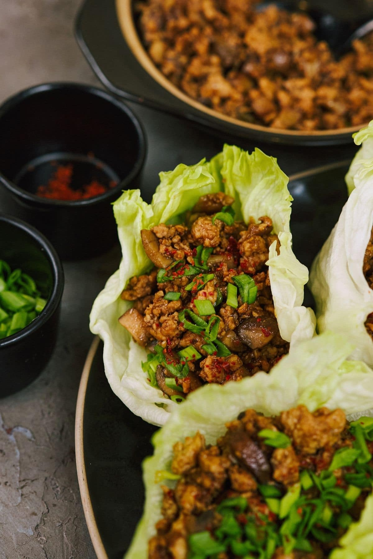 copycat P.F. Chang's teriyaki chicken lettuce wraps on plate with skillet of meat in background