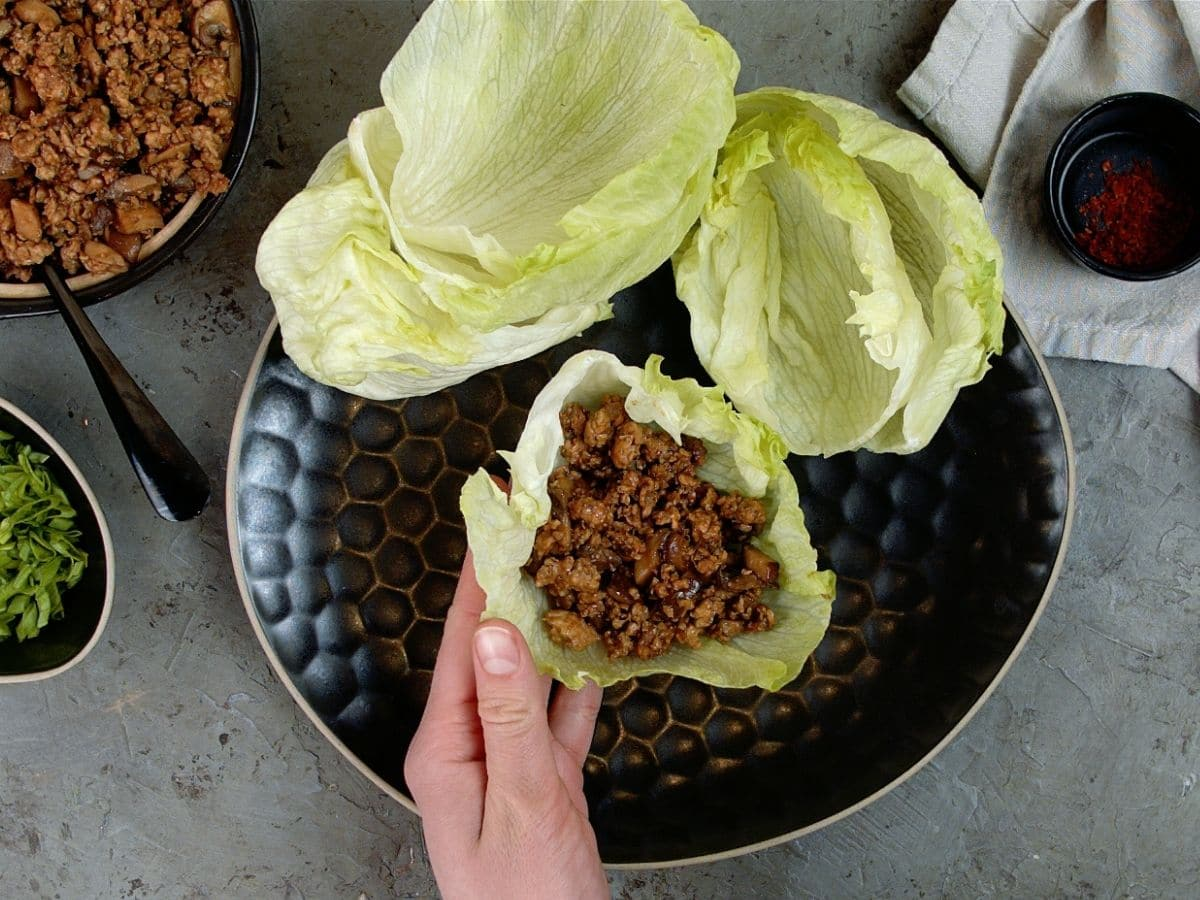 Hand filling lettuce leaf with chicken