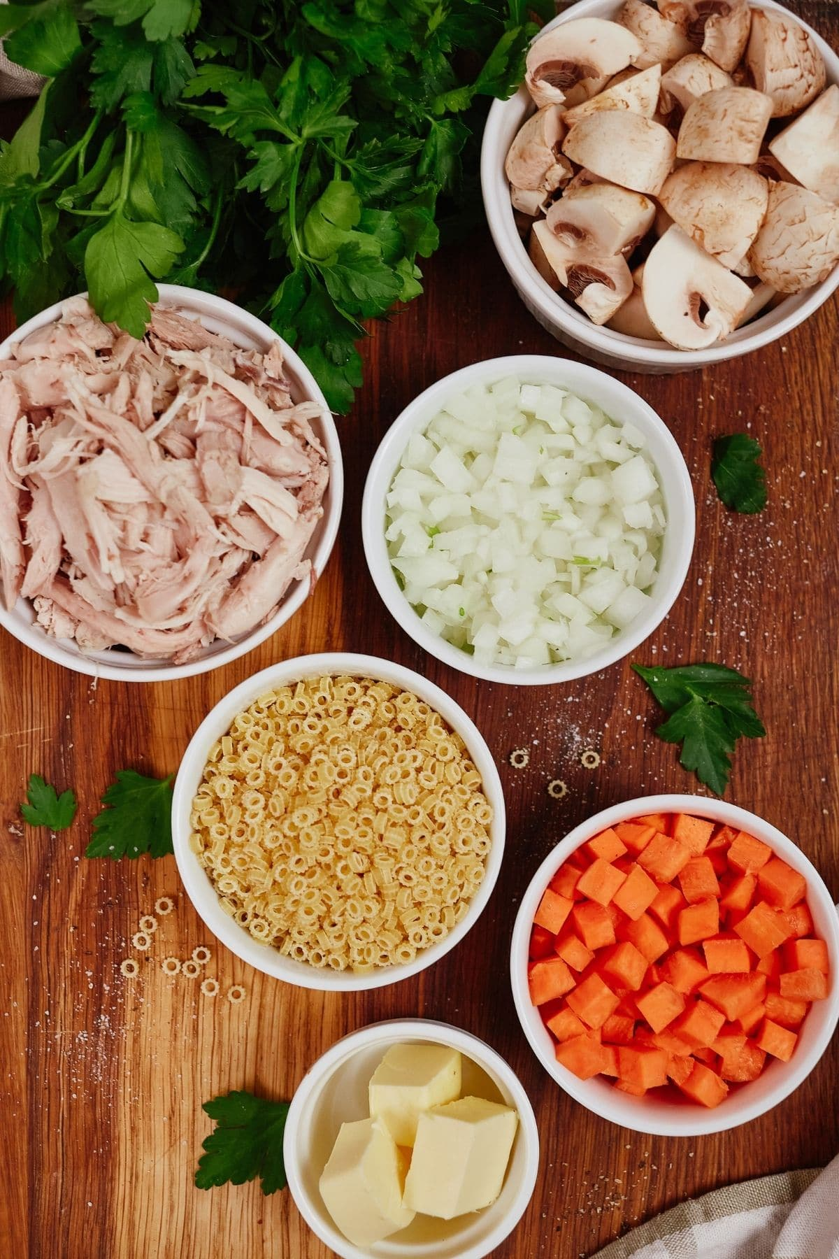 White bowls of vegetables and chicken on cutting board