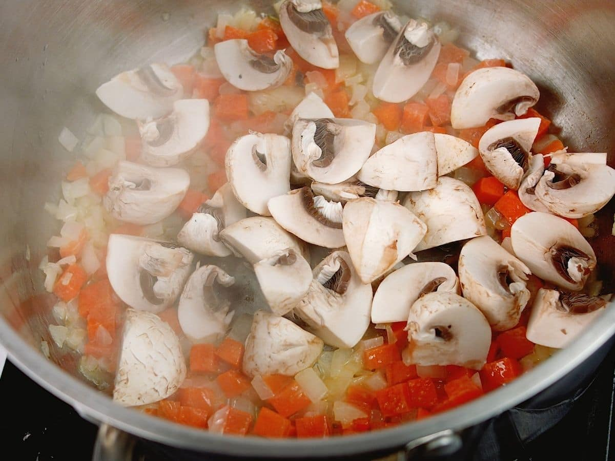 Mushrooms with carrots in pot on hot plate