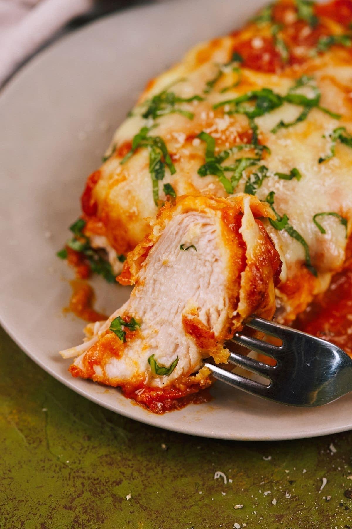 Fork holding chicken slice on plate