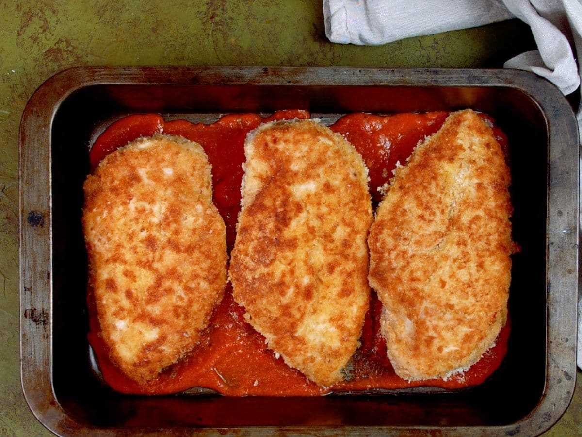 Fried chicken in pan with tomato sauce