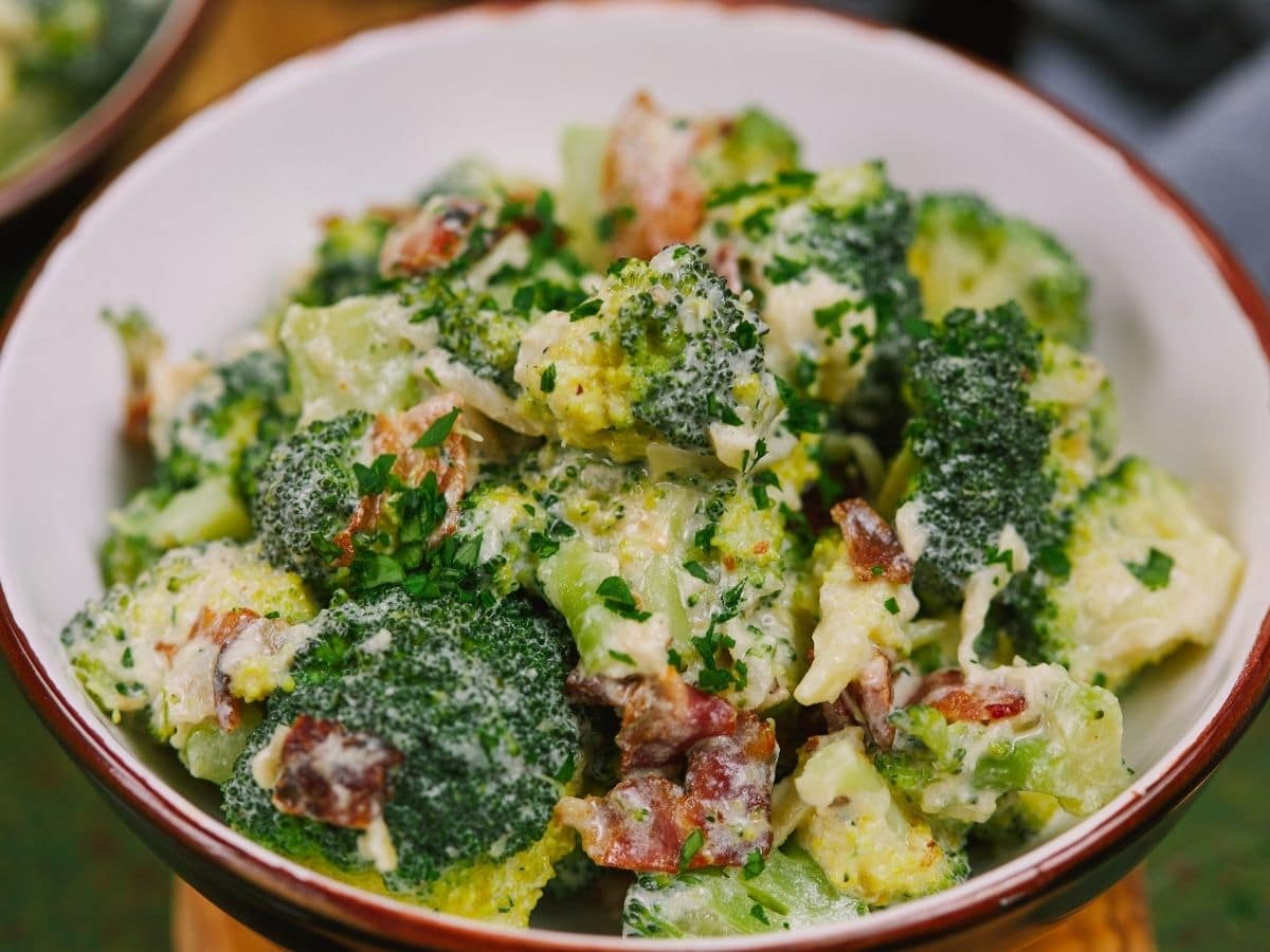 White bowl with red rim filled with creamy broccoli with bacon