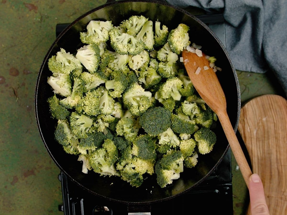 Wooden spoon stirring broccoli in cast iron skillet