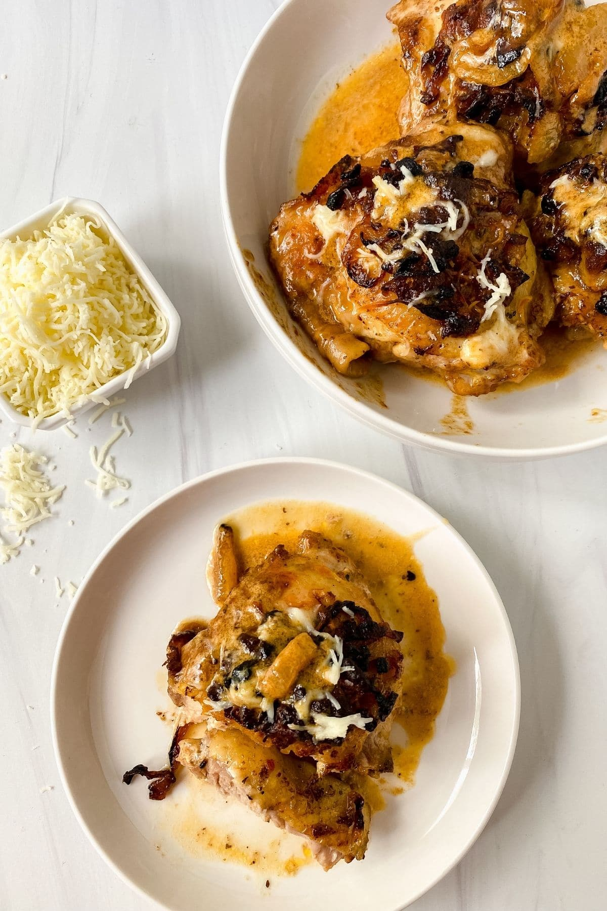 chicken thighs in sauce on white plates by bowl of parmesan