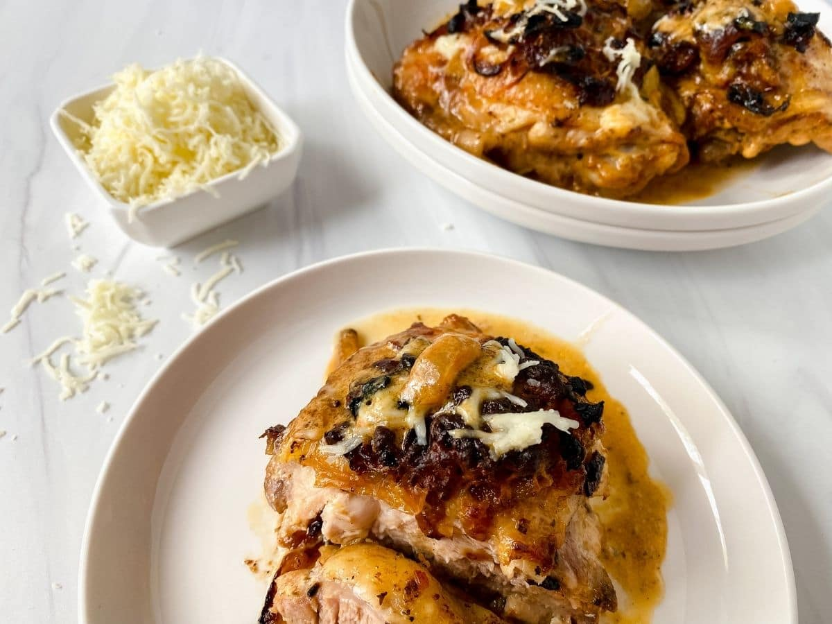 two white plates with chicken and onions by bowl of cheese