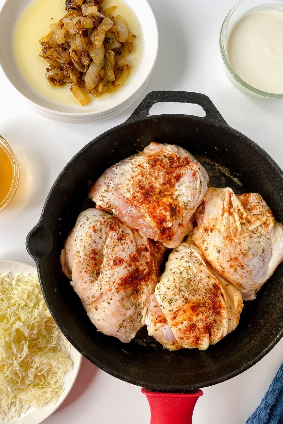 raw seasoned chicken thighs in cast iron skillet