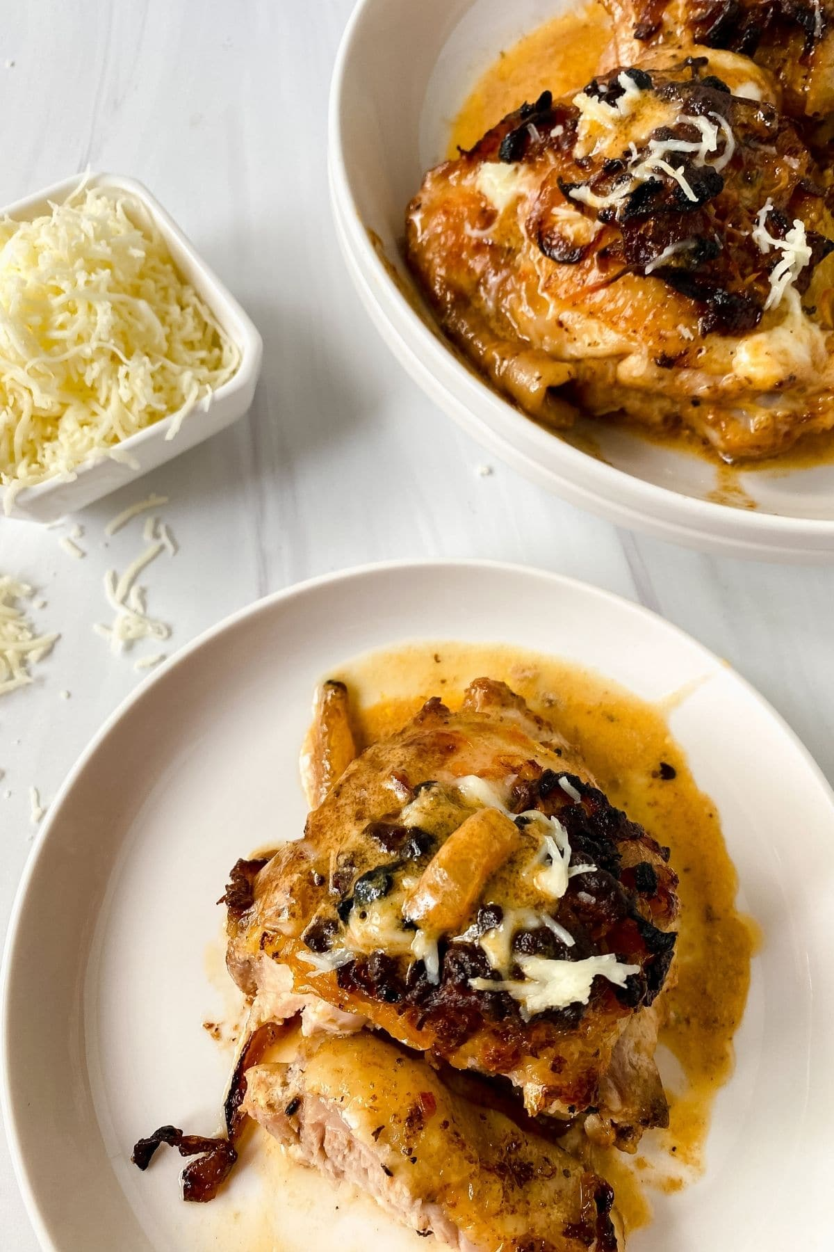 french onion chicken thighs on white plate on white table