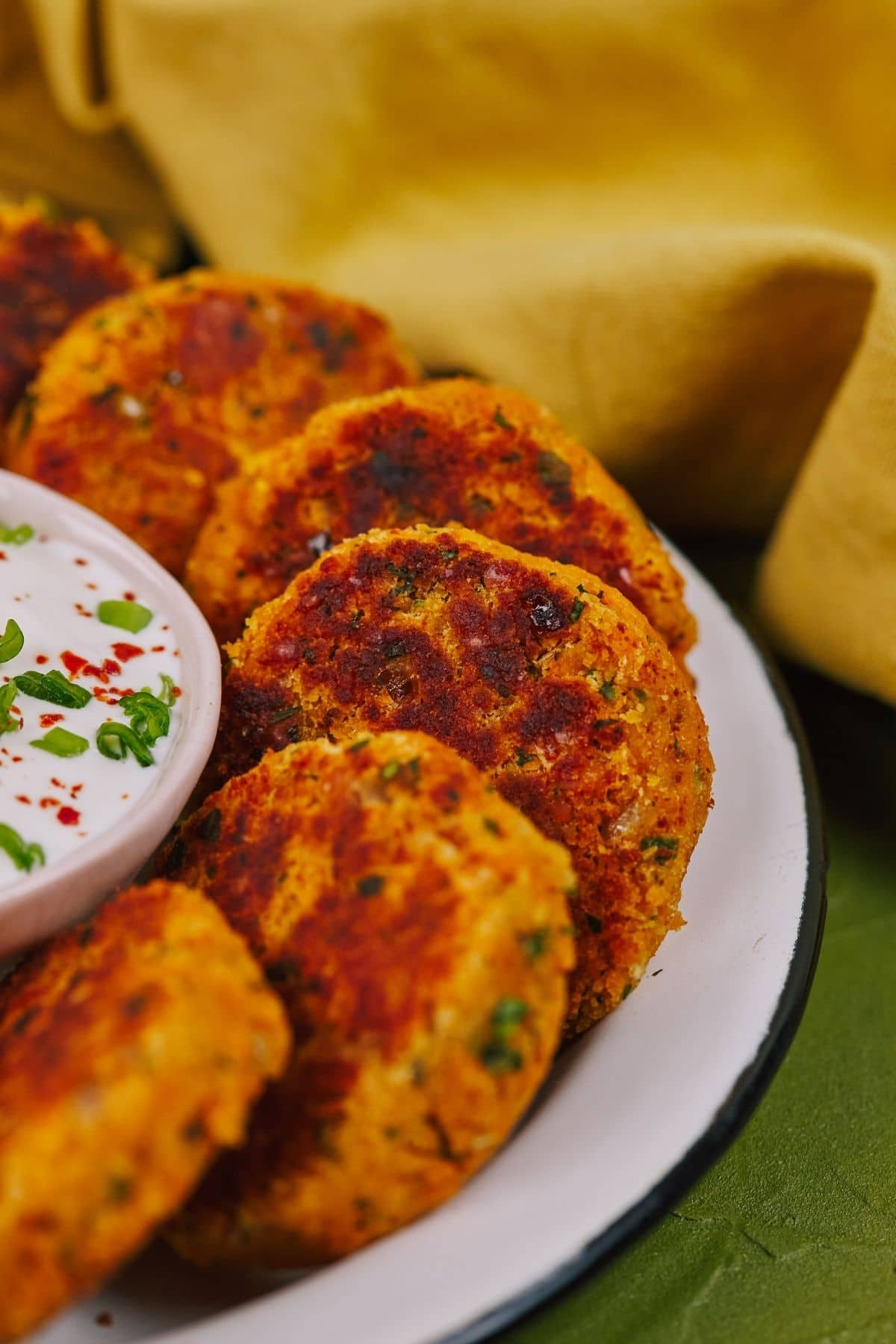 Side of white plate of vegetable fritters on green tablecloth