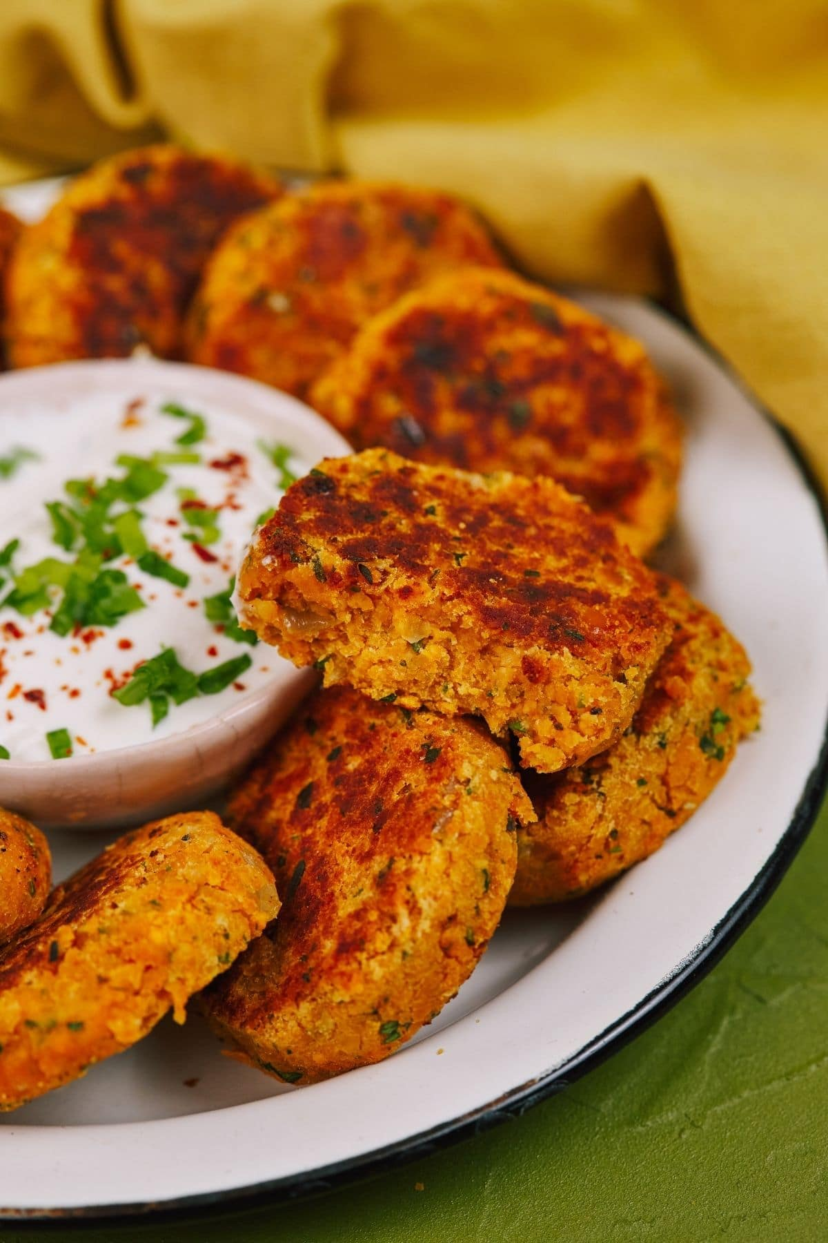 Fried veggie lentil patties on plate with bowl of dip topped with parsley