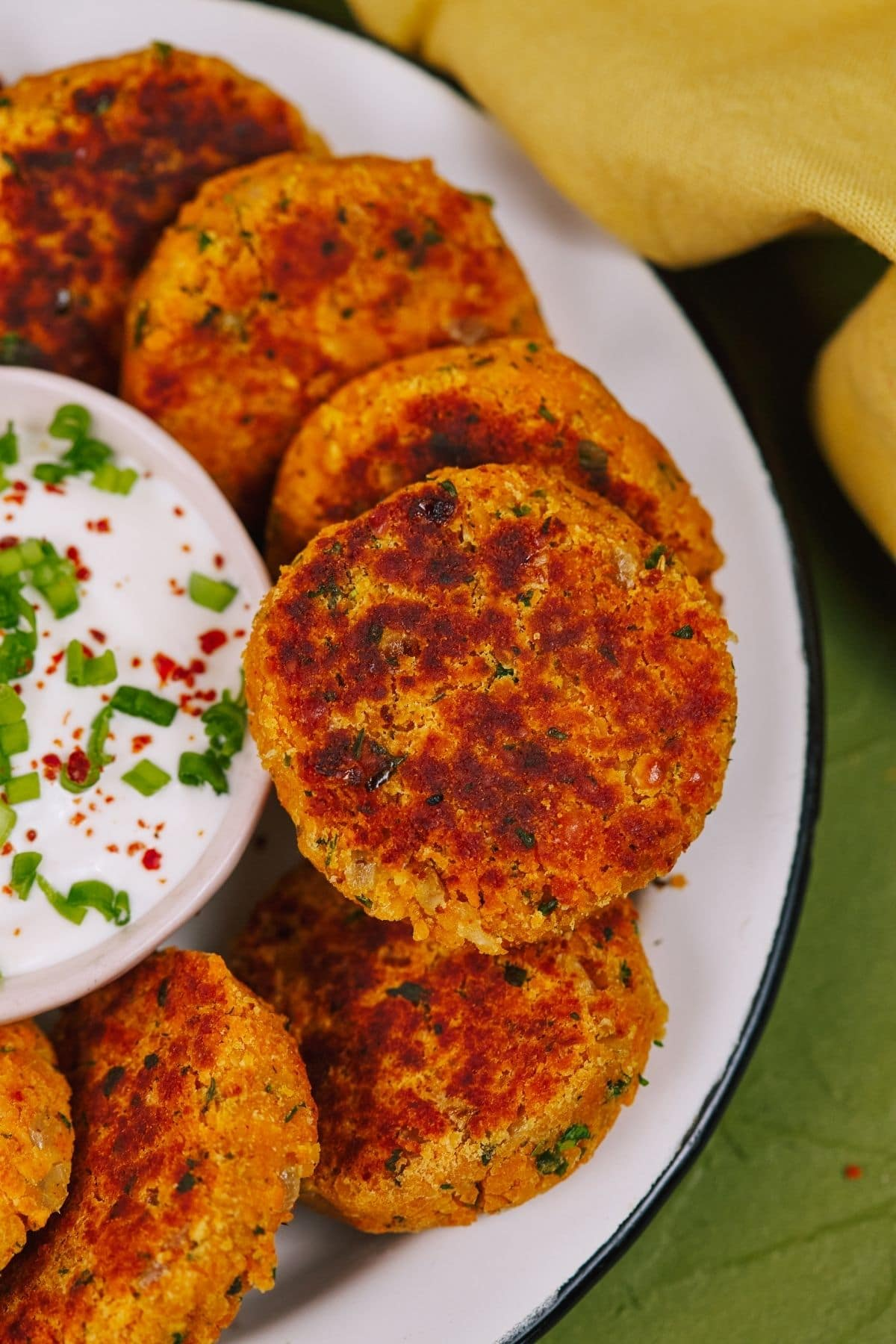 Stacked vegetable patties on white plate sitting on green tablecloth