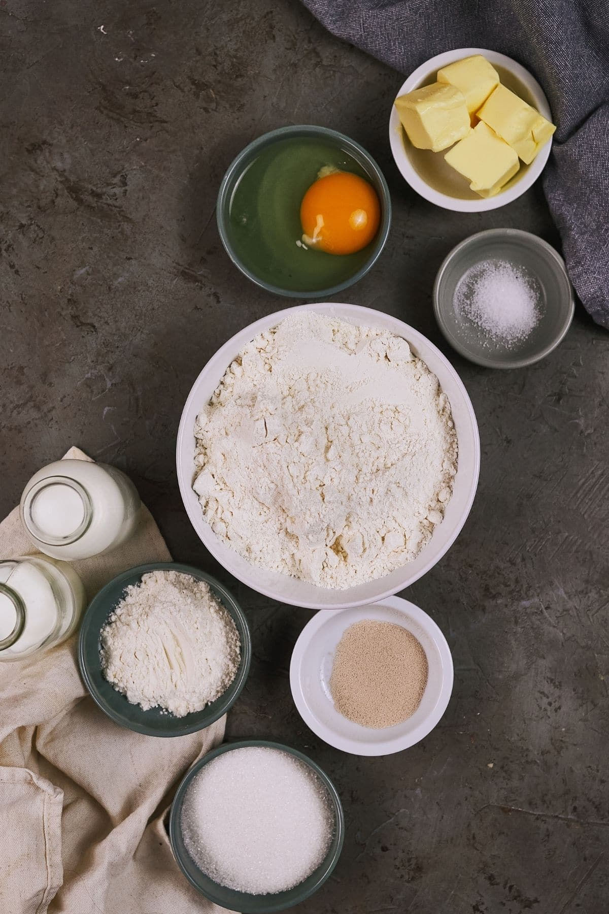 gray table with white and green bowls of flour eggs and salt
