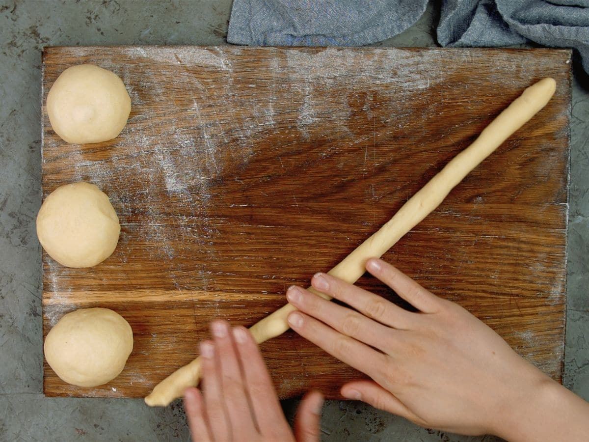 hands rolling dough into rope on cutting board