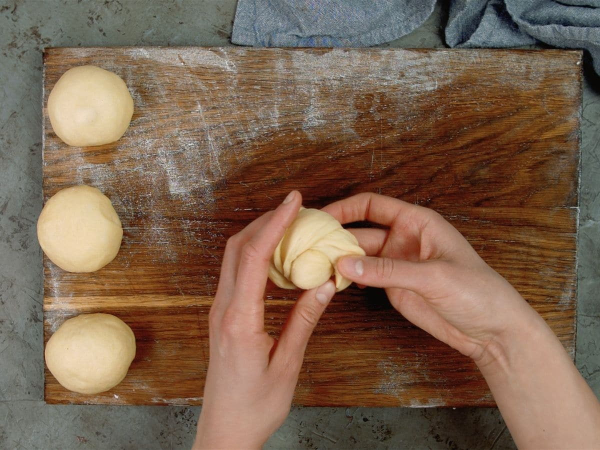 hands forming rope of dough into knot over cutting board