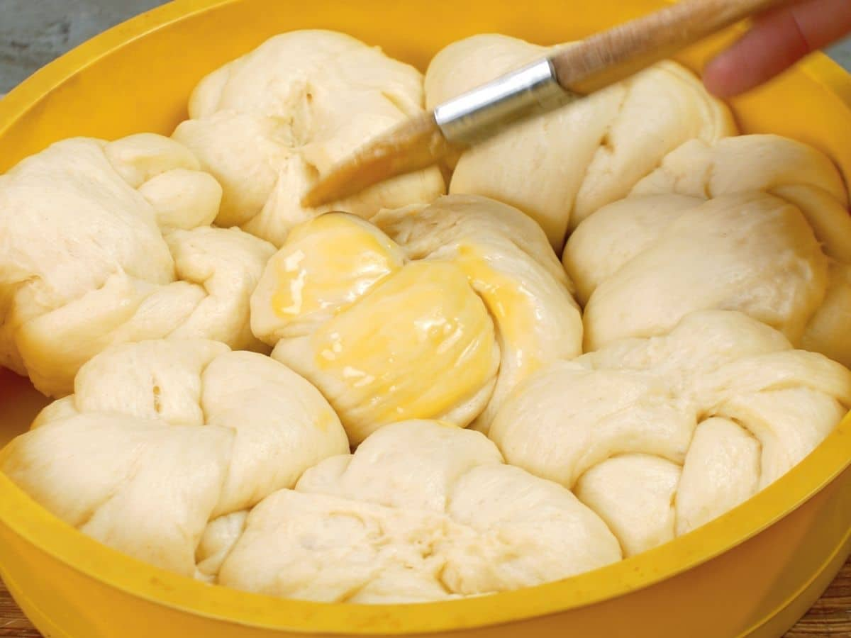 pastry brush putting egg wash onto raw bread dough knots
