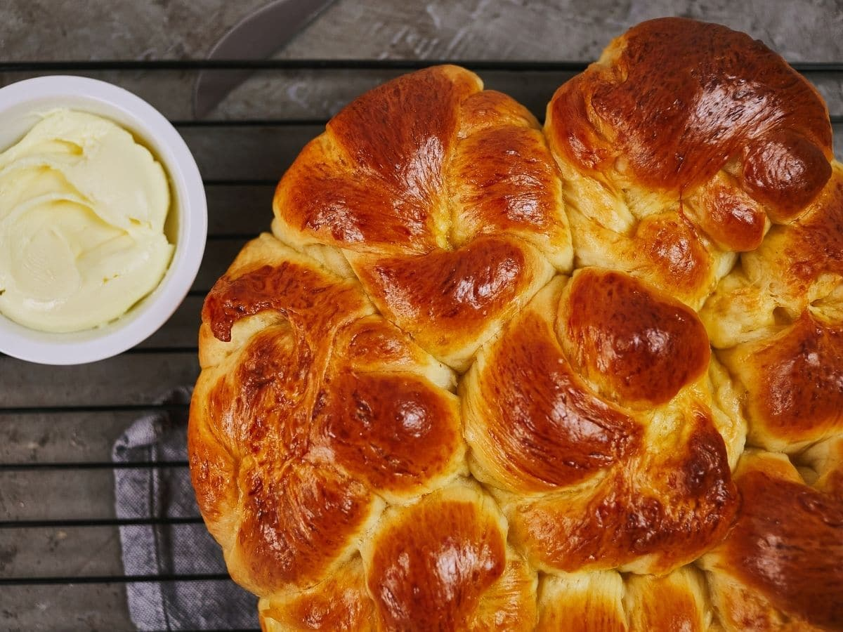 milk bread knots on rack by bowl of butter